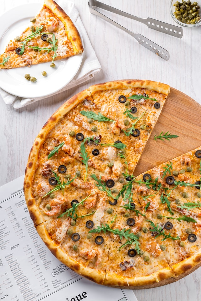 pizza on table with slicedpizza and tong
